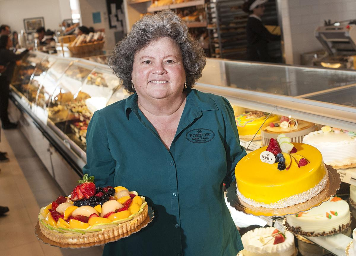 Betty Porto, who co-owns Porto's Bakery and Cafe with her family, holds up two cakes at their Downey location.