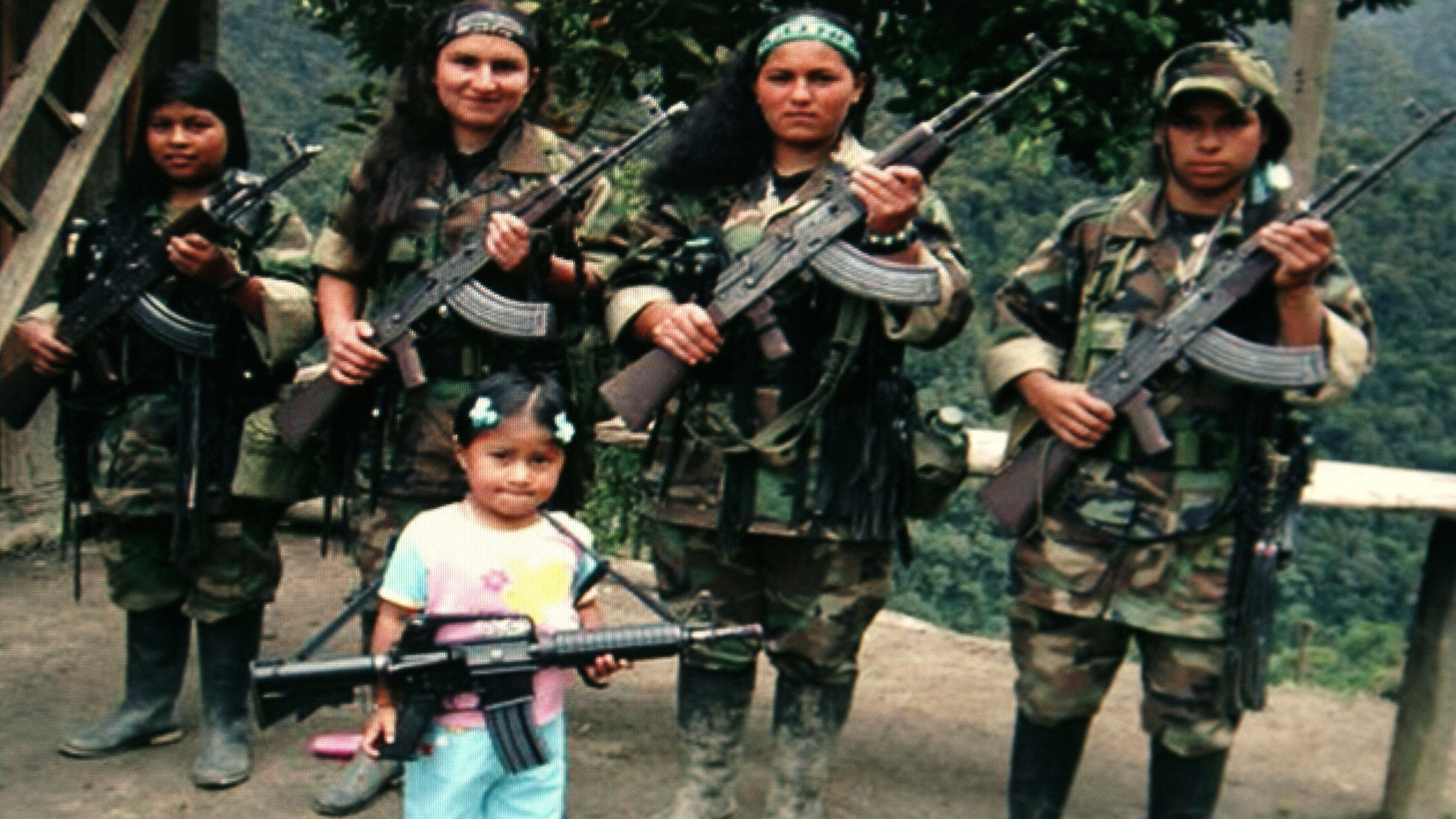 FARC rebels pose with an unidentified girl holding a weapon in southern Colombia in this undated photo confiscated by the Colombian police and released to the media on November 12, 2009. Police said that the photo was found on the body of a rebel killed in a combat against them on October 25, 2008. REUTERS/National Police/Handout   (COLOMBIA MILITARY CONFLICT CRIME LAW POLITICS) FOR EDITORIAL USE ONLY. NOT FOR SALE FOR MARKETING OR ADVERTISING CAMPAIGNS - RTXQNJ9