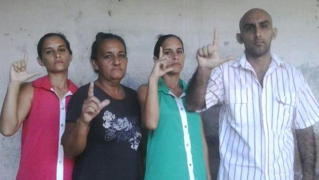 "Forming the sign ""L"" for ""Libertad"" are siblings Adairis Miranda, Maidolis Leyva Portelles (the siblings' mother), Anairis Miranda and Fidel Batista Leyva."