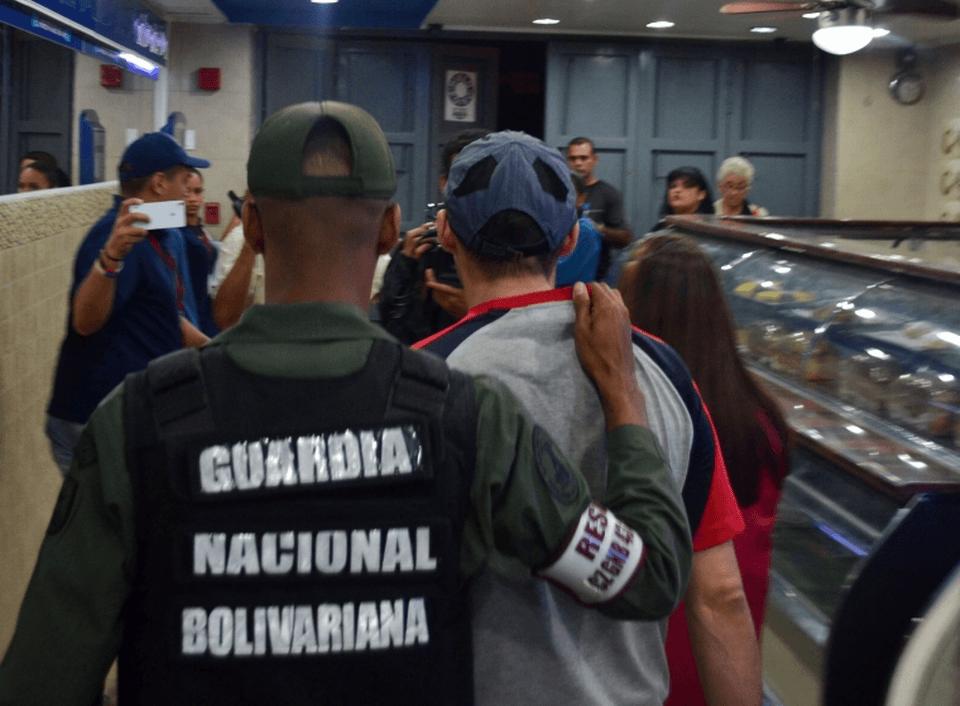 Venezuelan authorities escort an errant bread-maker out of a shop in Caracas.